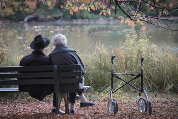 Senior couple man and woman are resting on a bench in the autumn park. Effect neutral and pastel...
