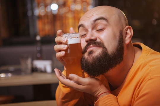 Close up of a happy bearded man cuddling with a glass of beer. Cheerful man loving his beer