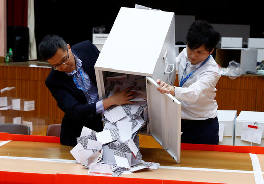 Officials open a ballot box at the polling station in the South Horizons West district as voting official closes in Hong Kong