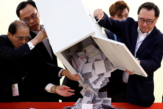 Officials open a ballot box at a polling station in Kowloon Tong, Hong Kong