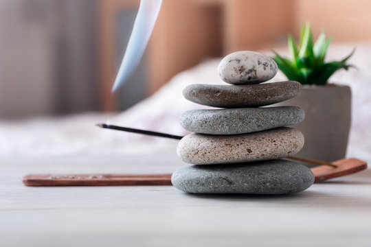 Relax, meditation process at home. Bedroom interior. Pyramid of zen stones, incense stick, flower.