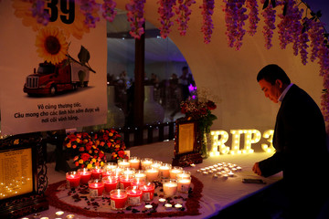 A man lights a candle at a make shift memorial at a fundraising event organised by Britain's Vietnamese community to raise money for the families of the 39 people found inside a container, at a conference venue near Wolverhampton, Britain