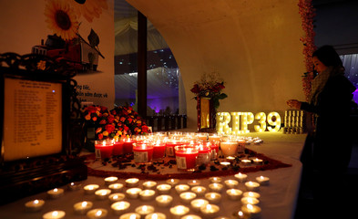 A woman lights a candle at a make shift memorial at a fundraising event organised by Britain's Vietnamese community to raise money for the families of the 39 people found inside a container, at a conference venue near Wolverhampton, Britain