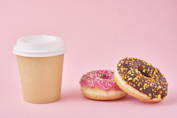 Cup of coffee and donuts on a pink background