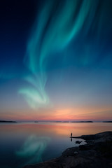 Silhouette of a man standing by a lake shore and looking at a beautiful aurora borealis on the sky...