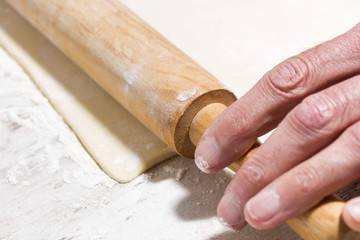 the process of rolling dough. hands and rolling pin, selective focus