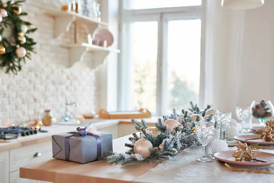 Interior light kitchen with christmas decor and tree. White kitchen in classic style. Christmas in the kitchen. Bright kitchen in white shades with Christmas. Christmas table setting.