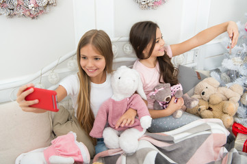I love selfie. Taking Christmas and New Year selfie with smartphone. Little girls use phone in bed. Happy little children with mobile phone. Merry Christmas and Happy New Year greetings