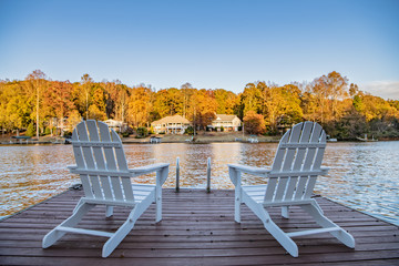 Adirondack style chairs on a dock, overlooking a beautiful, quiet, lake. Concept of a relaxing vacation in a remote area.