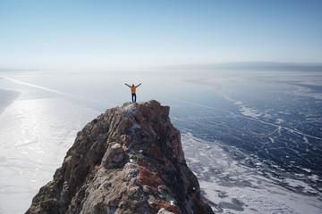 Lake Baikal at winter. Man standing on a cliff and looking at frozen Baikal lake.