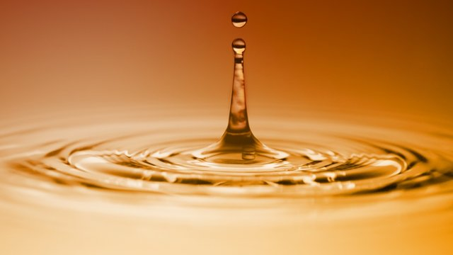 Macro close up photo of water drop colliding and bouncing the surface in orange golden ambient light environment.