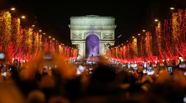 People on the Champs Elysees attend the launch of the Christmas holiday light show on the avenue leading up to the Arc de Triomphe in Paris