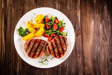 Grilled steak with baked potatoes and vegetables