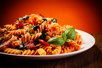 Fusilli with sausages and vegetables on wooden table