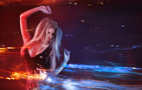 Young blonde woman dancing at night disco club. Motion blur