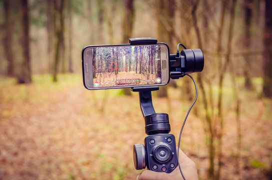 Close-up of a mobile phone and gimbal in the hands of a man on the background of a forest path. concept of blogging, shooting on the phone.
