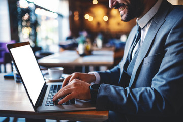 Cropped picture of good-looking smiling caucasian bearded businessman in suit sitting in cafe and using laptop for work.