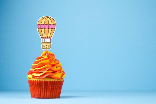 Cupcake with balloon. Travel concept. Dessert decorated red and yellow whipped cream on blue background.