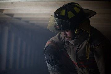 Fire Fighter kneeling down in wooden structure filled with smoke