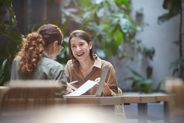 Portrait of cheerful young woman talking to friend or colleague during business meeting on outdoor cafe terrace, copy space