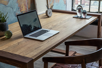 Stylish interior design of office space in loft apartment with wooden desk, chair, office supplies,...
