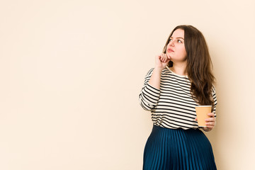 Young curvy woman holding a coffee looking sideways with doubtful and skeptical expression.