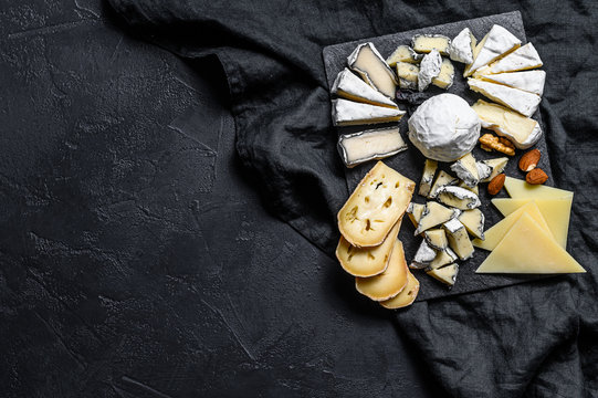 Cheese plate served with nuts and figs. Black background. Top view. Space for text