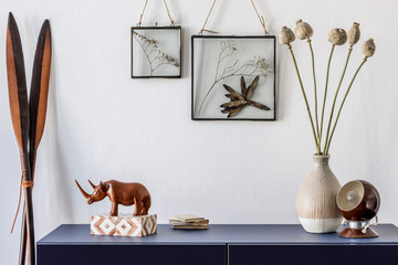 Modern scandinavian interior design with mock up photo frames, navy blue commode, flowers in vase, retro lamp and elegant accessories. Stylish home decor. Living room. Template Ready to use.