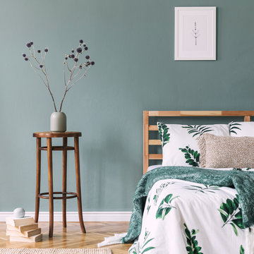Stylish and design composition of bedroom interior with wooden bed, mock up poster frame, chair, vase with flowers, and elegant accessories. Beautiful bed sheets, blanket and pillow. Template.