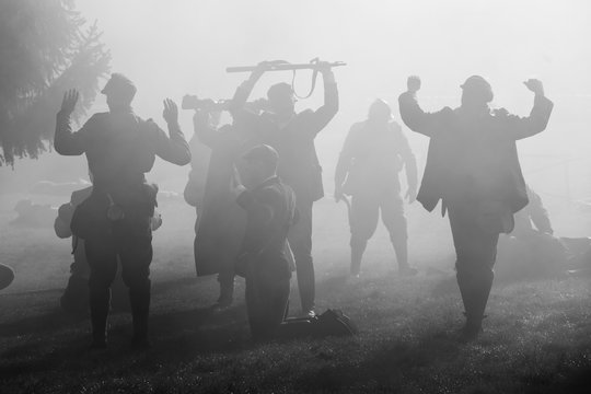 Silhouettes of Soldiers in uniforms during War with rifles on battlefield. All area is in smoke and sunrays peeking thru. There are hostages in the picture.