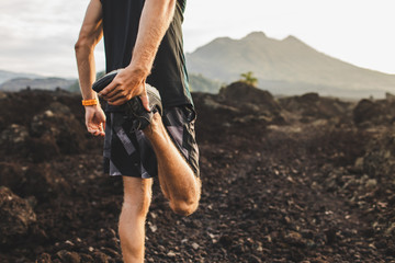 Runner stretching leg and feet and preparing for trail running outdoors. Active and healthy...