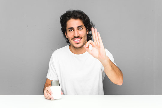 Young man holding an aftershave cream cheerful and confident showing ok gesture.