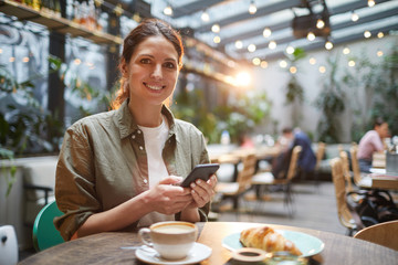 Portrait of beautiful young woman smiling at camera while using smartphone on outdoor terrace in cafe or coffee shop, copy space
