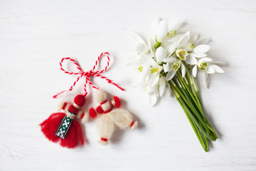 A bouquet of snowdrops and a red and white symbol of the holiday of the spring martenitsa