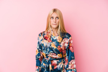Young blonde woman wearing a kimono pajama confused, feels doubtful and unsure.