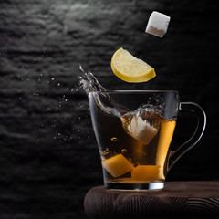 Slice of lemon and cubes of sugar falling in the glass tea cup. Frozen splashes. No people.