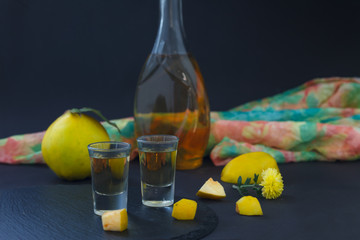 Quince brandy or quince vodka, hard liquor, strong drink in a bottle and glasses on dark background