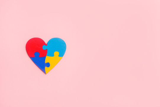 Puzzle pieces in form of heart, isolated on pink background. World Autism Awareness Day Concept