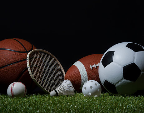 Sports equipment, rackets and balls on green grass with black background and copy space..