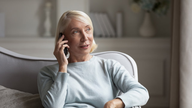 60s woman sit on couch holds phone chatting with friend
