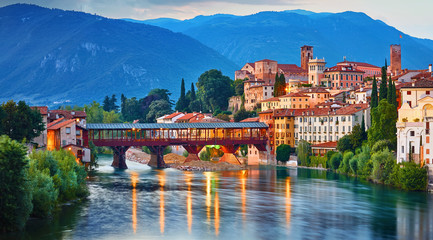 Photo sur Toile Retro Bridge Ponte degli Alpini at river Brenta Bassano del grappa Italy. Panoramic view at old town with vintage building and tower and wooden bridge at background Alpine mountains scenic landscape.