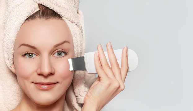 Young beautiful woman with pleasure treating skin with beauty device.  Female facial skin care concept
