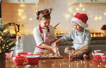 happy children boy and girl bake christmas cookies.