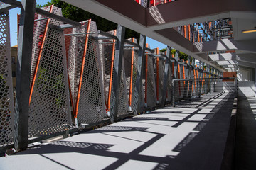 Perspective view of an interior walkway in a modern structure with railings, concrete beams, and perforated metal panels with orange trim