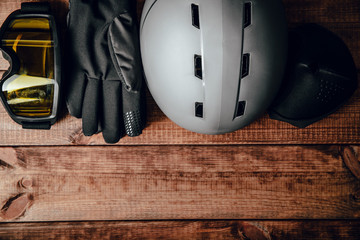 Skier's equipment, snowboarder. Ski helmet, ski goggles and gloves on a wooden background. The concept of skiing, proper clothing and preparation for winter sports.