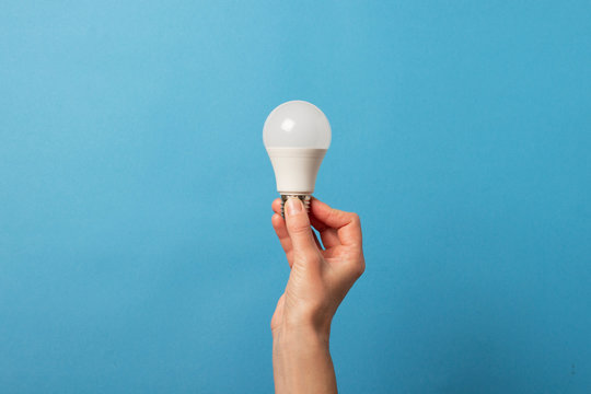 Female hand holds an LED lamp on a blue background. Energy saving concept, alternative energy sources, idea