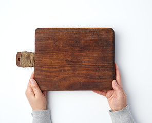 female hands holding an old empty wooden rectangular cutting board