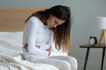 Unhealthy woman suffers from severe ache abdominal pain