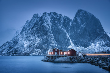 Red rorbu on sea coast and snow covered mountain at dusk. Lofoten islands, Norway. Moody winter landscape with traditional norwegian rorbuer, water, snowy rocks at night. Old fishermen's houses Wall mural