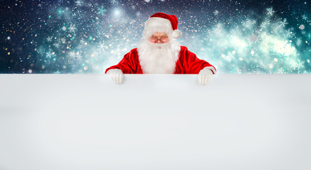 Happy Santa Claus holding Christmas blank advertisement banner background with copy space. Smiling Santa Claus pointing in white blank sign. Christmas theme, sales, space for your holiday text
